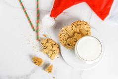 Milk and cookies for Santa Claus. Christmas concept, greeting card. Milk glass and cookies for Santa Claus with Santa`s hat on white marble background, copy Stock Images