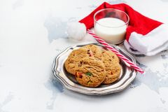 Milk and cookies for Santa Claus and Santa`s hat over wooden bac. Kground. Xmas concept, greeting card. Toned image royalty free stock photo