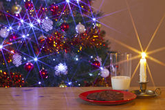 Milk and Cookies for Santa. A glass of milk and Cookies left out for Santa Claus on a table in front of the Christmas tree Royalty Free Stock Image