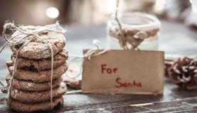 Milk and cookies for Santa. A stack of cookies and glass of milk for Santa on wooden background, concept Christmas and holiday Royalty Free Stock Photos
