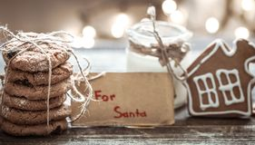 Milk and cookies for Santa. A stack of cookies and glass of milk for Santa on wooden background, concept Christmas and holiday Stock Image