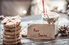 Milk and cookies for Santa. A stack of cookies and glass of milk for Santa on wooden background, concept Christmas and holiday Royalty Free Stock Images