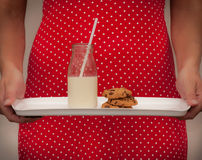 Milk and cookies served vintage style. Milk and cookies served on a tray by a lady in a vintage red polka dot dress Stock Image