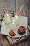 Milk and cookies. Milk in small jars with striped straws and cookies on vintage tray Royalty Free Stock Image