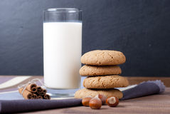Milk and cookies. Some cookies with glass of milk on dark background Royalty Free Stock Images