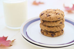 Milk and cookies in stack with seasonal decoration fall leaves. Selective focus Stock Image