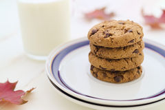 Milk and cookies in stack with seasonal decoration fall leaves. Selective focus Royalty Free Stock Images