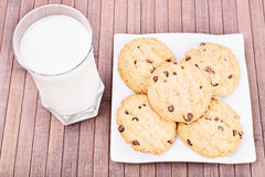 Milk and cookies on a wooden background Stock Images