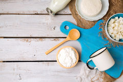Milk and cottage cheese with cutting board on rustic background. View from above. Stock Photos