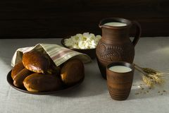 Milk, cottage cheese, pies in earthenware. Milk in a clay jug, cottage cheese and homemade fresh patties on a clay plate. Composition of dairy products and buns Stock Photo