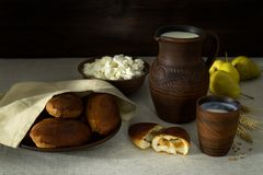 Milk, cottage cheese, pies in earthenware, pears. Milk in a clay jug, cottage cheese and homemade fresh patties on a clay plate, freshly harvested pears Stock Photography