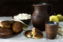 Milk, cottage cheese, pies in earthenware, pears. Milk in a clay jug, cottage cheese and homemade fresh patties on a clay plate, freshly harvested pears Stock Images