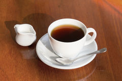 Milk and a cup of black coffee. On wooden table Royalty Free Stock Photos