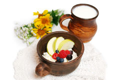 Milk and curd with summer fruits in brown ceramic bowls. Isolated on a white background Royalty Free Stock Photos