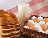 Milk, Eggs, & Bread - The Staples 2. A glass of milk, a loaf of sliced wheat bread and a bunch of brown and white eggs - the grocery list staples Royalty Free Stock Images