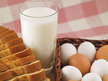 Milk, Eggs, & Bread - The Staples 4. A glass of milk, a loaf of sliced wheat bread and a bunch of brown and white eggs - the grocery list staples Royalty Free Stock Photo