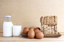 Milk, eggs, and bread on the wooden table. With copy space for text Stock Photos