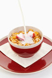 Milk falling on cornflakes with strawberry in red bowl on plate Royalty Free Stock Photos