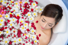 Milk and flower shawer. Spa Relaxation. Woman Body Care. Beautiful Sexy Asian Blonde Girl In Bikini Lying In Flower Bath In Resort Day Spa Salon. Beauty Royalty Free Stock Photo