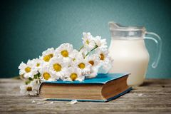 Milk and flowers on a wooden background Royalty Free Stock Photo