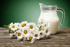 Milk and flowers on a wooden background Stock Photos