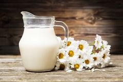 Milk and flowers on a wooden background Royalty Free Stock Photos