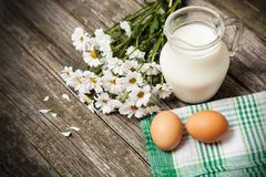 Milk and flowers on a wooden background Stock Images