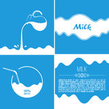 Milk flows from jug. Spray drops and white wave on blue background Stock Photos