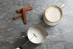 Milk frother over pitcher near cup of coffee stock photo