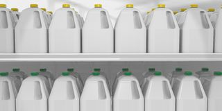 Milk gallon on shelve. Closeup of two shelves of gallon milk jugs displayed for sale at a supermarket Stock Photos