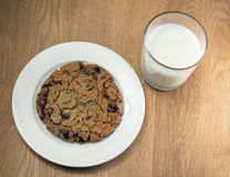 Milk and giant chocolate chip cookie. Afternoon snack of  milk, giant chocolate chip cookie and chocolate blocks on wooden background Stock Photography