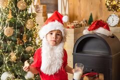 Milk and gingerbread cookie for Santa against Christmas light bokeh background. Kid Santa Claus takes a cookie on