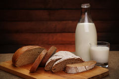 Milk in a glass bottle and rye bread Royalty Free Stock Image