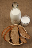 Milk in a glass bottle and rye bread Stock Image