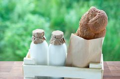 Milk in glass bottles and bread in a kraft bag in a wooden box against stock images