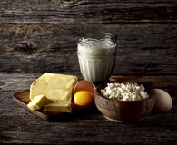 Milk in glass, butter and eggs on a wooden background. Cottage c royalty free stock image