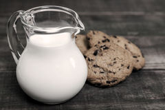 Milk in glass jug and biscuits. Homemade corn and oat biscuits with chocolate and milk in glass jug Stock Photo