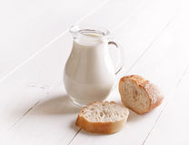 Milk in glass jug and bread Stock Image