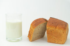 Milk in a glass on a light background with fresh crusted bread. Royalty Free Stock Image