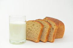 Milk in a glass on a light background with fresh crusted bread. Stock Images