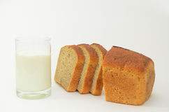 Milk in a glass on a light background with fresh crusted bread. Stock Photo