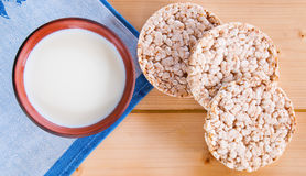 Milk in glass mug with crispbread on wooden table. Royalty Free Stock Image