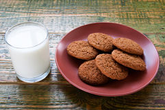 Milk in glass mug with oatmeal cookies on wooden table. Royalty Free Stock Image
