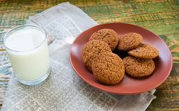 Milk in glass mug with oatmeal cookies on wooden table. Stock Photos