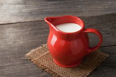 Milk in glass pitcher on white background. Wooden table Stock Photos