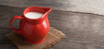 Milk in glass pitcher on white background wooden table.  stock image