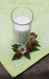 Milk glass with raspberry and daisies on a wooden table Royalty Free Stock Image