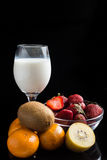Milk in grass and mix fruits on the black Royalty Free Stock Photography