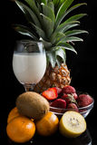 Milk in grass and mix fruits on the black. Royalty Free Stock Photos