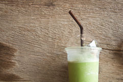 Milk Green tea smoothie in plastic cup. Wood background stock photo